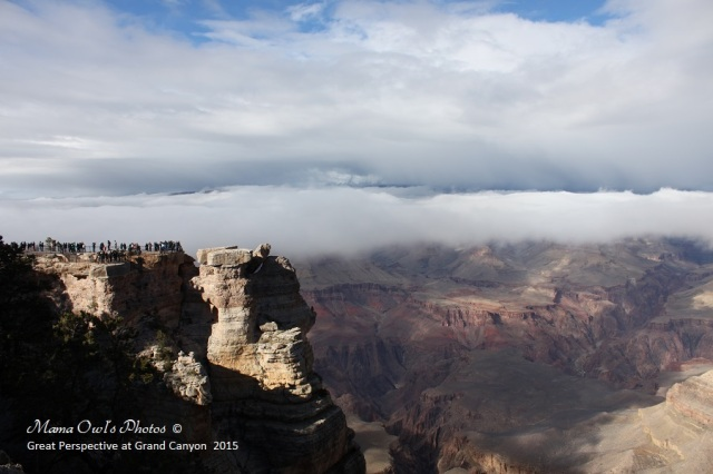 A good persepctive of the size of the Grand Canyon compared to several people standing on an outlook point.